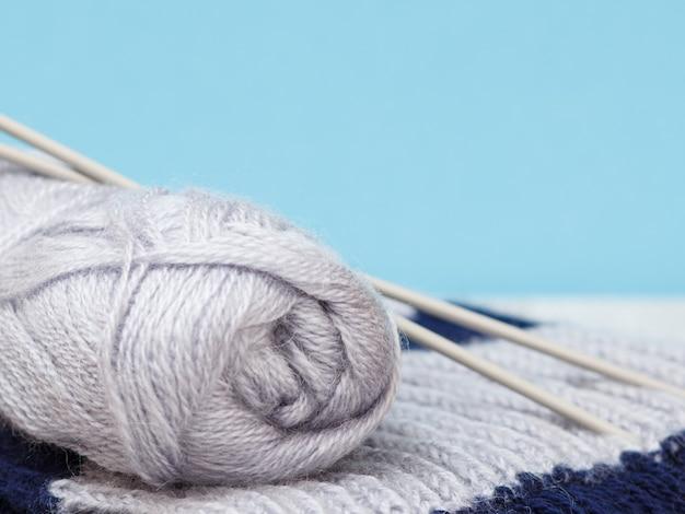 Vista ravvicinata della matassa di filato e sciarpa con ferri da maglia in metallo su sfondo blu. profondità di campo. concetto di maglieria.