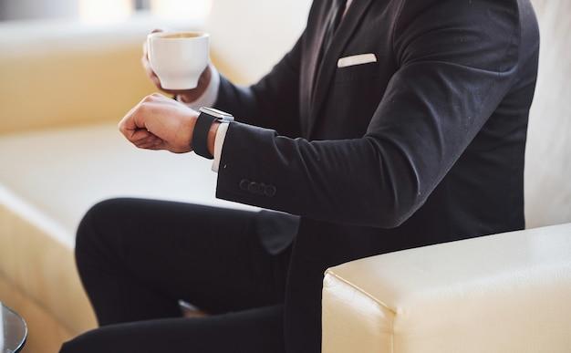 Vista ravvicinata del giovane uomo d'affari in abito nero e cravatta con tazza f bevanda controllando il tempo.