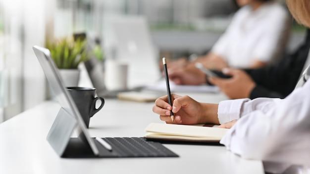 Vista del primo piano di giovane donna di affari che lavora al suo piano che scrive l'idea sul taccuino con la compressa digitale.