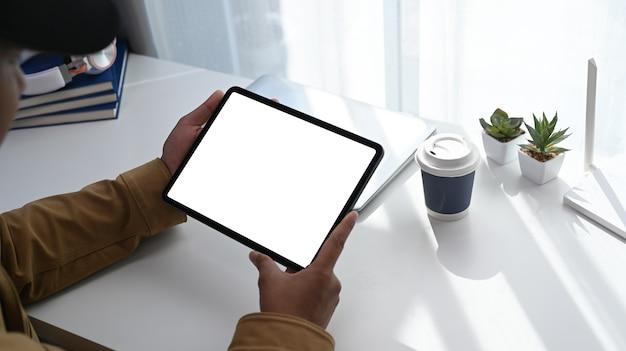 Vista ravvicinata delle mani del giovane utilizzando la tavoletta digitale sul suo spazio di lavoro vicino alla finestra con il chiarore del sole.