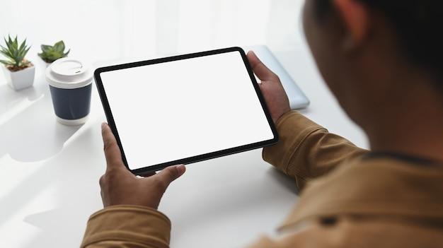 Vista ravvicinata del giovane hans che tiene in mano una tavoletta digitale con schermo bianco. schermo vuoto per il testo pubblicitario.
