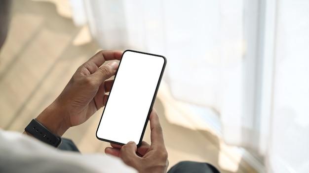 Vista ravvicinata del giovane uomo seduto vicino alla finestra e tenendo mock up smart phone con schermo bianco
