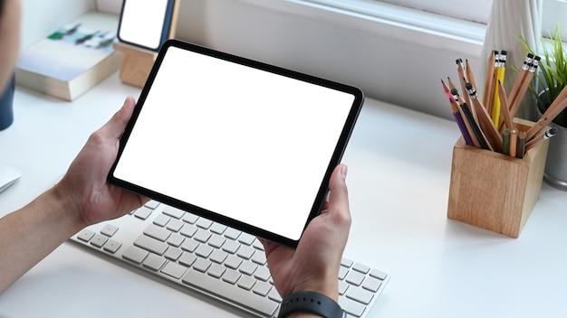 Vista ravvicinata del giovane che utilizza la tavoletta digitale navigando in internet.