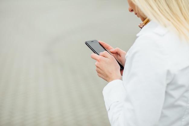 Chiuda sulla giovane donna di vista in una grande città facendo uso del telefono con lo spazio della copia.