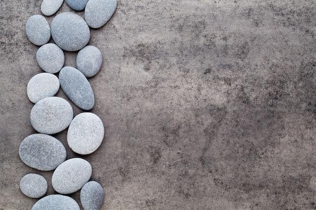 Vista ravvicinata di oggetti a tema pietre zen su sfondo grigio.