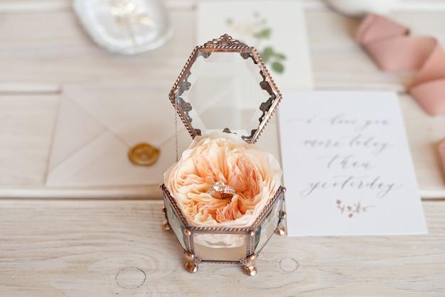 Contenitore di gioielli di nozze d'annata del primo piano per le fedi nuziali su una tavola di legno con una cartolina d'auguri e fiori.