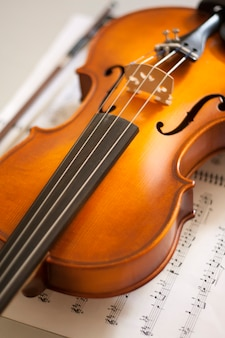 Primo piano del violino che si appoggia sullo spartito. strumenti a corda. concetto di musica classica.