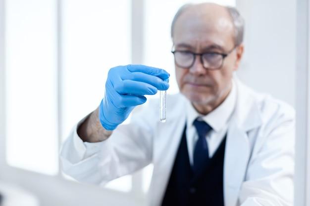Primo piano del virus in provetta tenuto da uno scienziato senior in un laboratorio medico sterile. ricercatore viorolog in un laboratorio professionale che lavora per scoprire cure mediche.