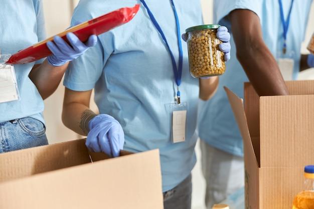 Primo piano di volontario in guanti protettivi che tengono un barattolo di piselli durante lo smistamento e l'imballaggio degli alimenti