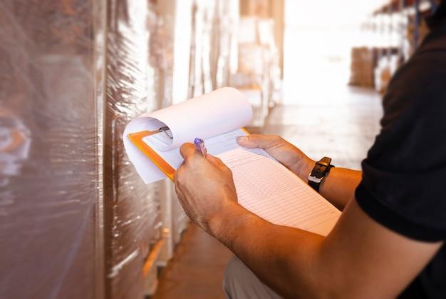 Primo piano, operaio del magazzino che tiene appunti mentre fa la gestione dell'inventario del prodotto. controllo stock, spedizione merci, stoccaggio magazzino.