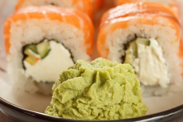 Close up wasabi con rotoli di sushi uramaki philadelphia sullo sfondo sul piatto di ceramica. cucina giapponese. profondità di campo