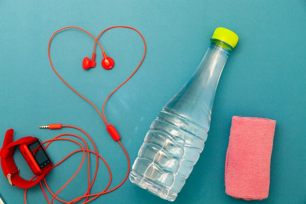 Primo piano di una bottiglia d'acqua, orologio e auricolari rossi, asciugamano su sfondo verde. concetto di sfondo fitness.