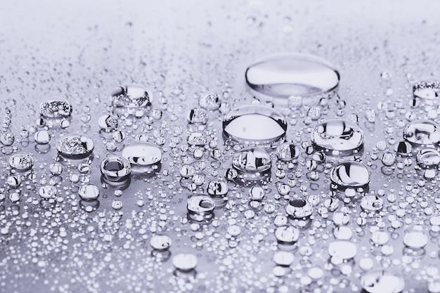 Primo piano di gocce d'acqua su sfondo argento