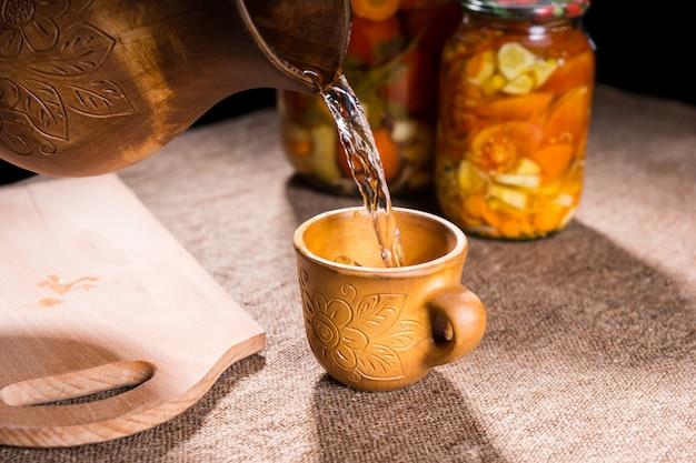 Close up di acqua versando in legno intagliato bicchiere da brocca sul tavolo coperto di tela con vasetti di conserve vegetali sottaceto e tagliere di legno in background