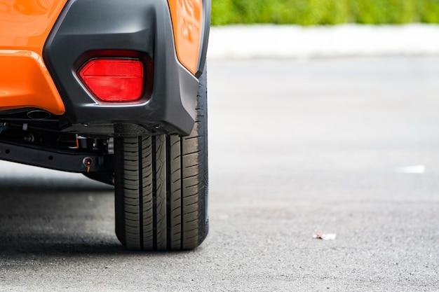 Primo piano ruota dell'auto arancione sulla strada