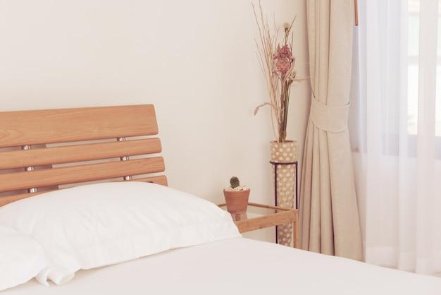 Chiuda sulla decorazione interna della camera da letto bianca con il vaso di fiori del cactus sul tavolino di wwoden