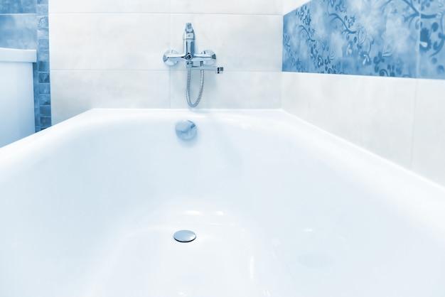 Primo piano della vasca da bagno bianca e blu nell'interno del bagno