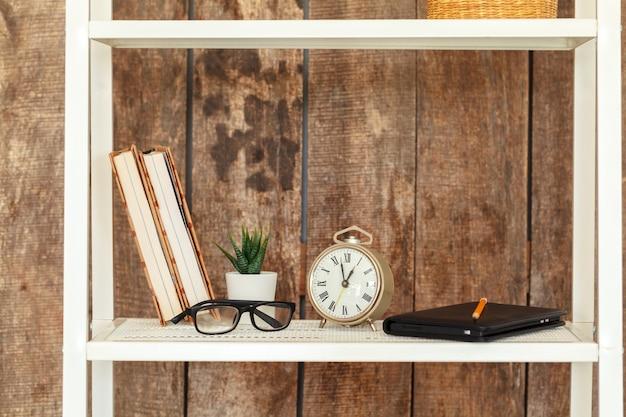 Primo piano di scaffale bianco contro la parete di legno del grunge