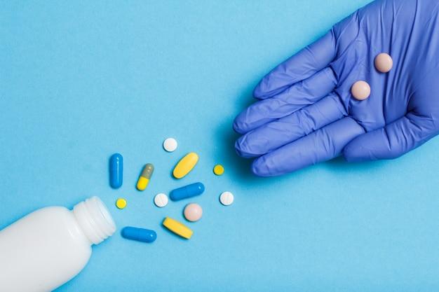 Primo piano bottiglia bianca con diverse pillole e capsule e mano di dottoressa in guanto di lattice blu con pillole sul palmo. concetto di negozio di droga legale. vista dall'alto