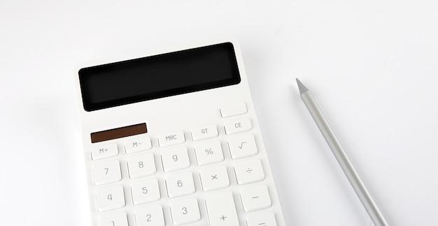 Primo piano calcolatrice bianca con penna su sfondo bianco