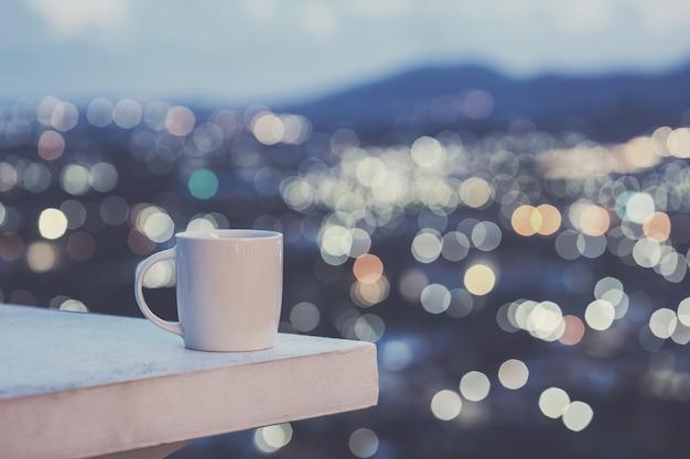 Chiuda sulla tazza di caffè macchiato sul contro e sul bokeh variopinto della luce della sfuocatura del fondo della città