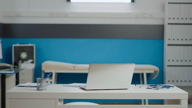 Primo piano della scrivania bianca con laptop e strumenti medici