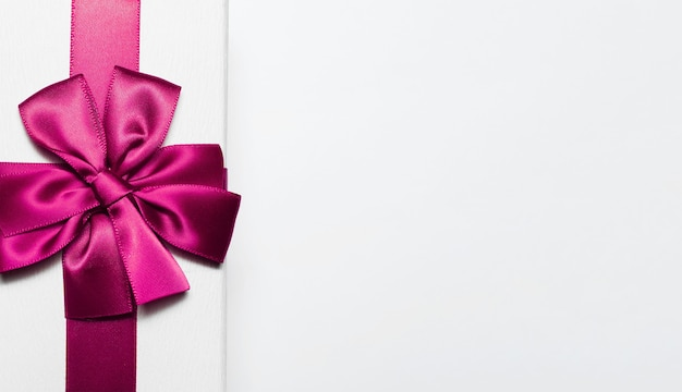 Primo piano del contenitore di regalo bianco con fiocco rosa isolato su superficie bianca