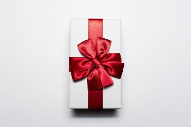 Close-up di confezione regalo bianca con fiocco rosso, isolato su sfondo bianco.