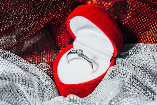 Primo piano di un anello di fidanzamento in oro bianco con diamanti nel riquadro rosso, concetto di amore