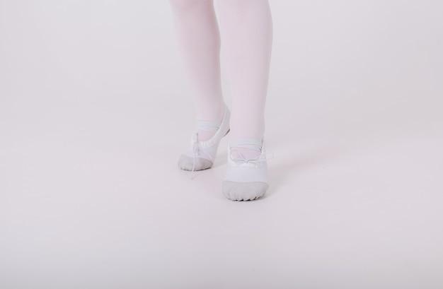 Primo piano di piccole scarpe da punta bianche di una ragazza ballerina su un muro bianco