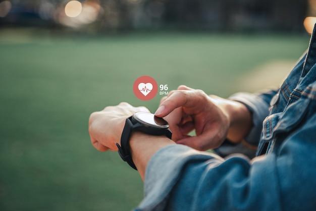 Chiuda sull'orologio astuto bianco con l'icona frequenza cardiaca