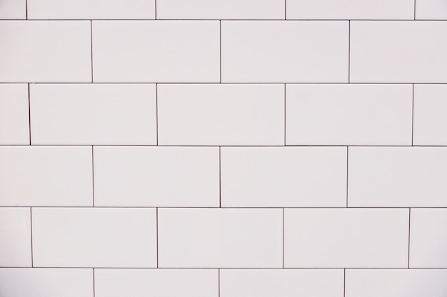 Chiuda sulla parete d'annata bianca delle mattonelle del mattone ceramico