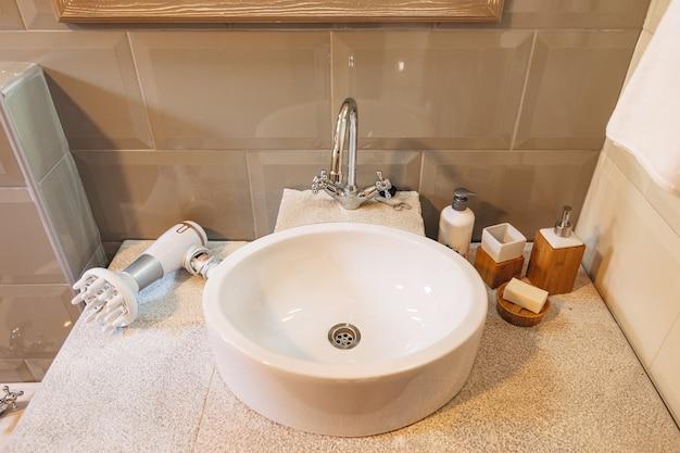 Primo piano di un lavandino bianco con sapone, prodotti per l'igiene e un asciugacapelli sul piano di lavoro