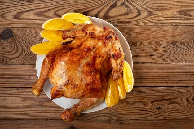 Close-up intero pollo fritto al forno con arance e carote su un piatto bianco su un tavolo di legno marrone.