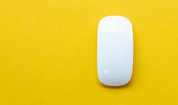 Primo piano del mouse in vetro wireless su sfondo giallo, vista dall'alto