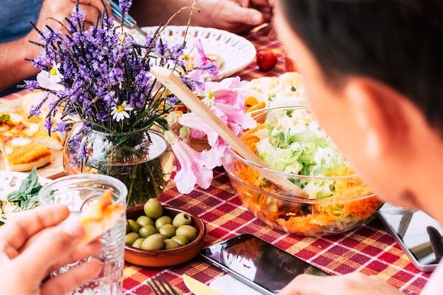 Primo piano con persone amici mangiare e divertirsi insieme pranzando su un tavolo pieno di cibo Foto Premium