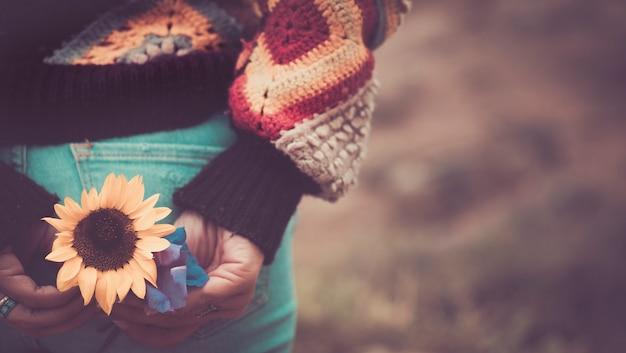 Primo piano con toni vintage e colori del fiore del sole sulla tasca posteriore del retro dei jeans da donna casual. immagine concettuale di pace e amore per lo stile hippy e godersi la natura e lo stile di vita tutti insieme