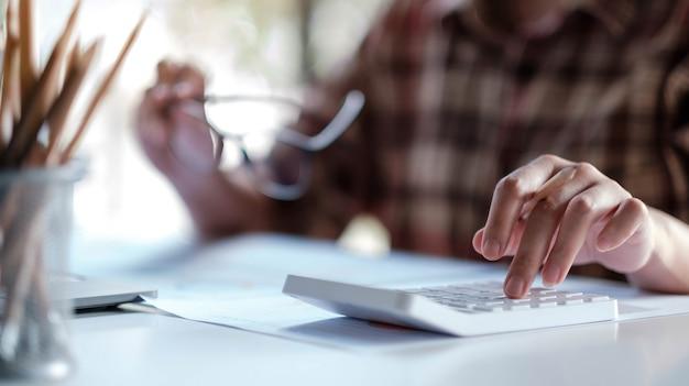 Primo piano di una donna o di un contabile che tiene la penna che lavora sulla calcolatrice per calcolare i dati aziendali, il documento contabile e il computer portatile in ufficio at