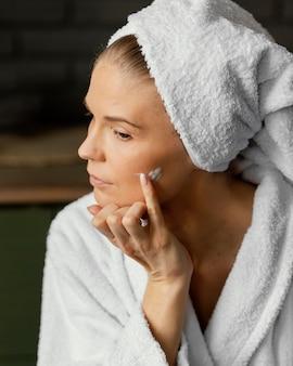 Chiuda sulla donna che applica crema per il viso