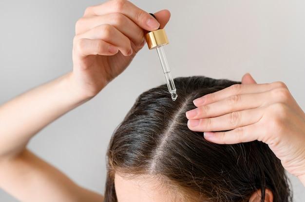 Donna del primo piano che applica siero per capelli