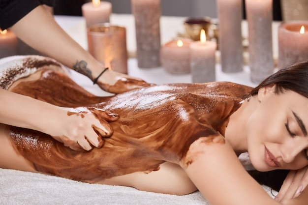 Primo piano della parte posteriore della donna con cioccolato e olio durante la terapia di massaggio nel salone della stazione termale