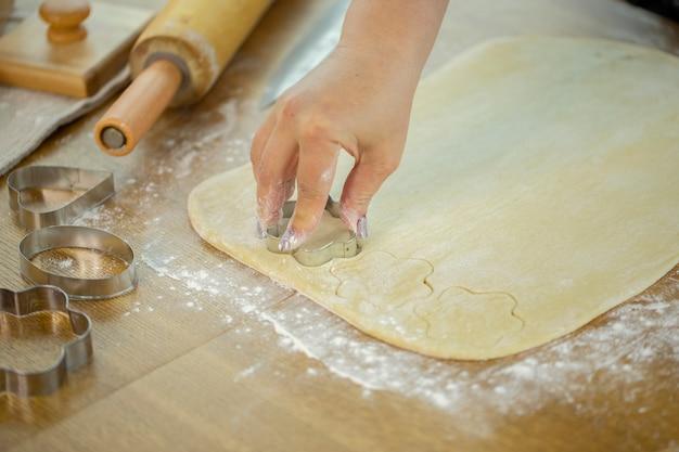 Chiuda sui biscotti di zucchero di cottura della donna