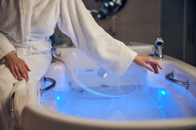 Primo piano su una donna in accappatoio che raggiunge un maniglione nella vasca da bagno