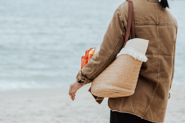 Primo piano di una donna sulla spiaggia con in mano una borsa da spiaggia durante una giornata luminosa, spazio copia, vacanza e concetto di libertà freedom