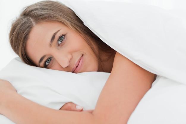 Primo piano, donna a letto, testa sul cuscino e impaziente