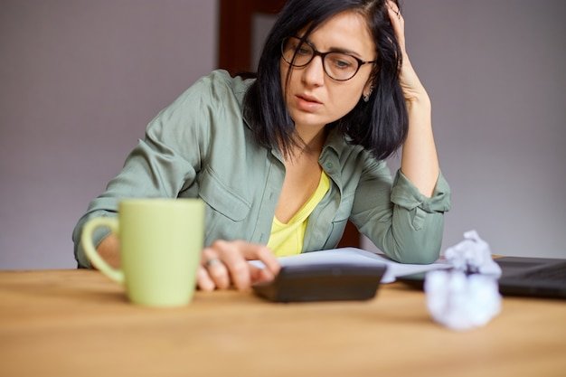 Primo piano di donna calcola le spese sulla calcolatrice al tavolo di legno