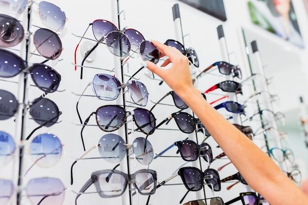 Primo piano della donna che controlla gli occhiali da sole