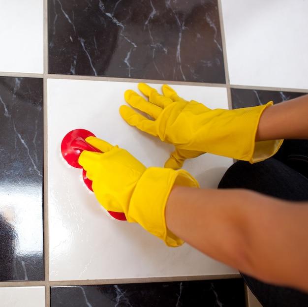 Primo piano di una donna che pulisce il pavimento di un bagno
