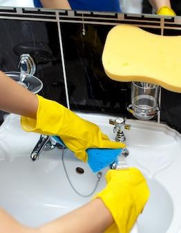 Primo piano di una donna che pulisce il lavandino di un bagno