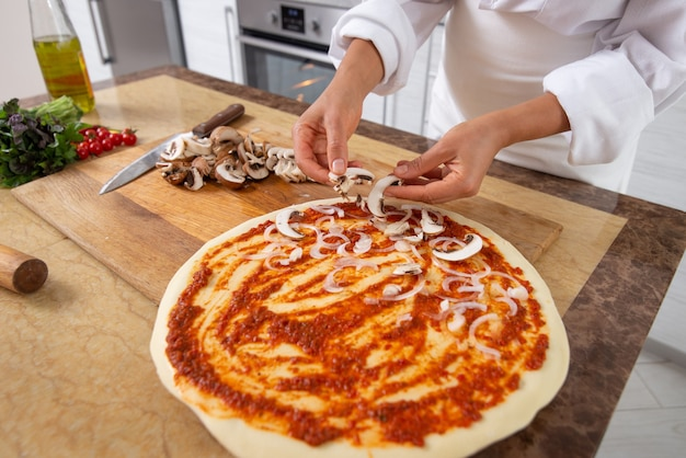 Vicino donna che cucina la pizza
